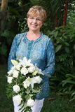 Mature woman with flowers Stock Image
