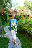 Mature woman with flowers. Royalty Free Stock Photos