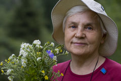 Mature woman with flowers. On a green background Stock Images