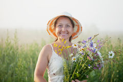Mature woman with flowers posy. In summer field Stock Image