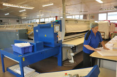 Commercial laundry. Mature woman folding sheets at a commercial laundry in Greymouth, New Zealand Royalty Free Stock Photos