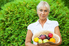 Mature woman with fruits Stock Photos