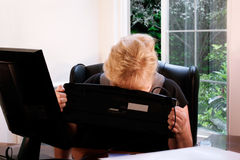 Mature woman frustrated in office Stock Photography
