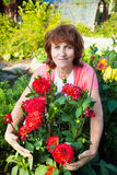 Mature Woman in the garden cares for flowers Stock Photos