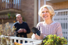 Mature woman gardening in patio. Mature women in patio with gardening accessories with her husband in the background royalty free stock photography