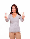 Mature woman gesturing victory sign with fingers Royalty Free Stock Images