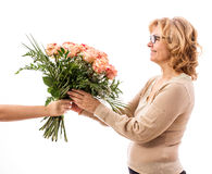 Mature woman gets bouquet of roses, Mother`s Day. Mature woman gets a bouquet of roses, Mother`s Day, isolated Stock Photo