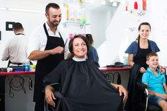 Mature woman getting hairdo of male hairdresser. Mature women getting hairdo of male hairdresser in beauty salon Royalty Free Stock Images