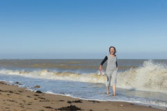 Mature woman getting splashed in the sea. Active mature walking and having fun in the sea and getting splashed Stock Photo