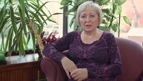 Mature woman give an interview. Senior woman sits in the armchair and talk about her life. Prores codec stock video