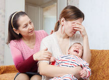 Mature woman gives solace to crying adult daughter Stock Photos