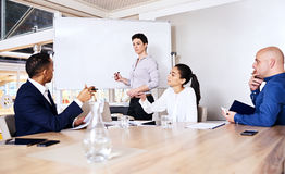 Mature woman giving a business presentation to three potential investors royalty free stock photo