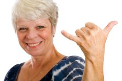 Mature woman giving a hang loose sign. Royalty Free Stock Images