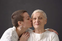 Mature woman giving a kiss at senior woman Stock Image