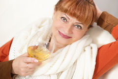 Mature woman with a glass of wine on sofa. Mature woman with scarf and glass of wine on sofa Stock Photos