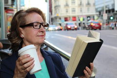 Mature woman with glasses drinking coffee and reading book sitting indoor in urban cafe. Cafe city lifestyle with traffic lights Stock Photography