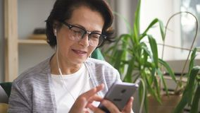 Mature woman in glasses and earphones scrolling screen