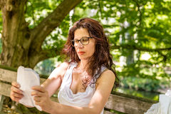 Mature woman with glasses reads paper Royalty Free Stock Photos