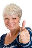 Mature Woman with Good News. A pretty, mature, white haired woman giving a thumb up as a sign of good news Stock Photo