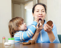 Mature woman with granddaughter puts facepowder Royalty Free Stock Photo