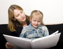 Mature woman with granddaughter reading book at Royalty Free Stock Photos