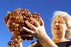 Mature woman and grapes Royalty Free Stock Photos