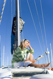 Mature woman, in green striped jumper, sitting on deck of yacht moored at harbour jetty, reading magazine, profile Royalty Free Stock Photo