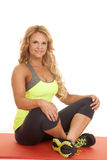 Mature woman green tank sit crosslegged. A woman in a green tank sitting on a fitness mat Royalty Free Stock Image