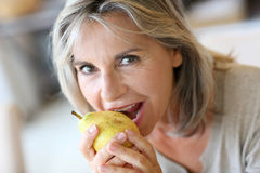 Mature woman with grey hair eating a pear Royalty Free Stock Images