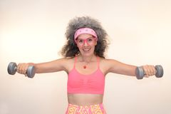 Woman working out shoulders dumbbells 80s retro look. A mature woman with grey hair is working out her shoulders with dumbbells. Bandana sweatband, retro glasses royalty free stock photography