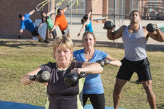 Mature Woman and Group Exercising Outdoors Stock Photos