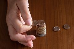 Mature woman hand putting coins into a pile on wooden table. Closeup. European euro coins, poverty concept. Counting royalty free stock photo