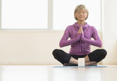 Mature Woman With Hands Clasped Meditating At Home Stock Photography