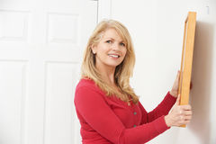 Mature Woman Hanging Picture On Wall stock images