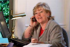 Mature woman happy conversation. Mature businesswoman laughs during phone conversation Stock Image