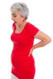 Mature woman has backache - isolated - red clothes Royalty Free Stock Photos