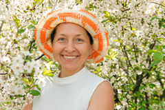 Mature woman in hat. Beautiful mature woman on background of the cherry blossoms stock photography
