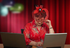Mature woman in hat staring at the computer screen Stock Photography