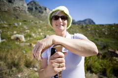 Mature woman, in hat and sunglasses, hiking on mountain trail, leaning on hiking pole, smiling, portrait royalty free stock image
