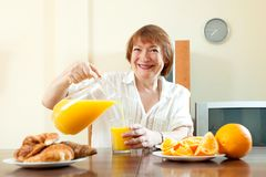 Mature  woman having breakfast Royalty Free Stock Photos