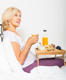 Mature woman having breakfast Royalty Free Stock Photography