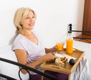 Mature woman having   breakfast in bed Stock Photos