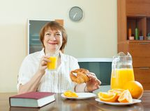 Mature  woman having breakfast with book Stock Photos
