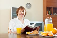 Mature  woman having breakfast with book Stock Images