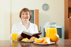 Mature  woman having breakfast with book Stock Photo