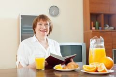 Mature  woman having breakfast with book Royalty Free Stock Images