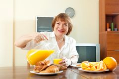 Mature  woman having breakfast Royalty Free Stock Images