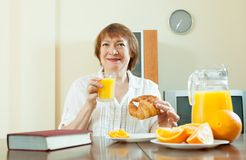 Mature  woman having breakfast with juice Royalty Free Stock Image