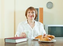 Mature  woman having breakfast with milk Royalty Free Stock Photos