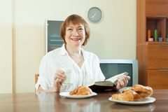 Mature  woman having breakfast with milk at home Stock Image